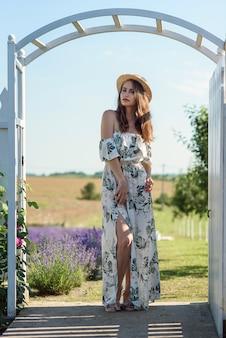 Encantadora mujer hermosa con sombrero de paja y vestido de verano con flores en el jardín de lavanda del patio trasero.