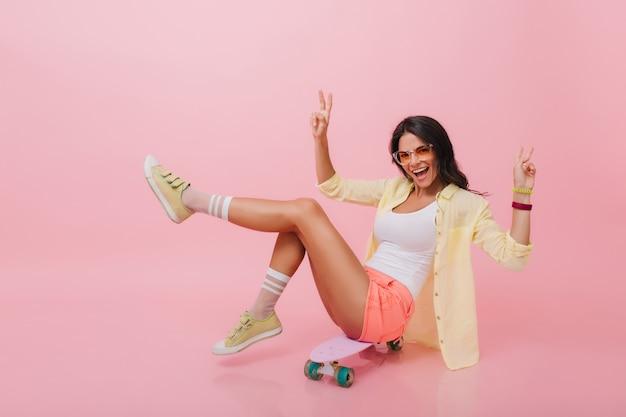 Encantadora mujer hispana con piel bronceada en pantalones cortos de mezclilla divirtiéndose durante el verano interior. chica asiática guapa con longboard pasar tiempo libre.