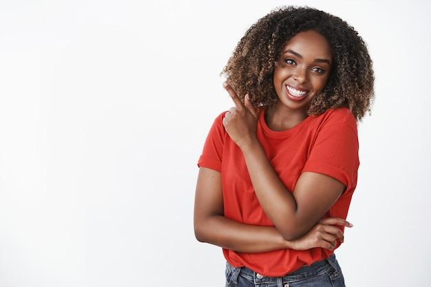 Encantadora mujer joven afroamericana despreocupada, coqueta y femenina con el pelo rizado en camiseta roja sonriendo alegremente apuntando a la esquina superior izquierda sobre la pared blanca