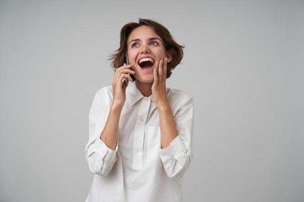 Encantadora mujer joven atractiva con cabello castaño corto hablando por teléfono y recibiendo buenas noticias, levantando felizmente su palma hacia la cara, de pie con ropa formal