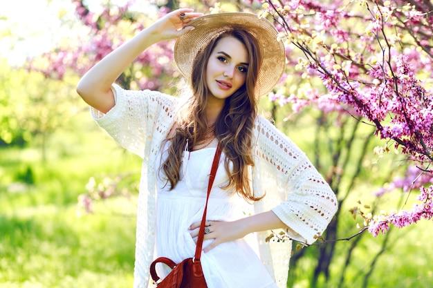 Encantadora mujer joven y bonita con pelo largo con sombrero de verano, vestido de luz blanca caminando en el soleado jardín sobre fondo floreciente de sakura. relajación, sonreír a la cámara, ropa ligera, sensible, alegría