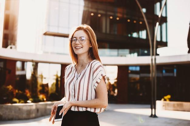 Encantadora mujer joven con cabello rojo y pecas mirando a la cámara riendo contra un edificio moderno