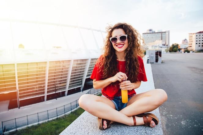 Encantadora mujer joven divertida en gafas de sol sentado en la losa de mármol
