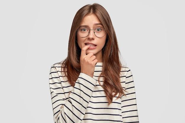 Encantadora mujer joven con expresión pensativa muerde el dedo, vestida con un suéter a rayas, lleva gafas redondas, posa contra la pared blanca. estudiante femenina preocupada pensativa piensa en algo