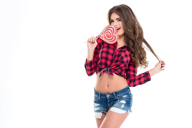 Encantadora mujer joven feliz con el pelo largo y rizado en camisa a cuadros y pantalones cortos de jeans comiendo piruleta en forma de corazón sobre pared blanca