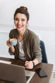 Encantadora mujer joven con ordenador portátil mientras está sentado en el interior, tomando café