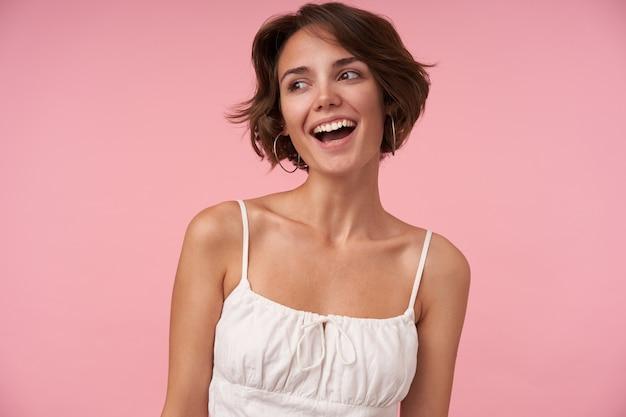 Encantadora mujer joven con peinado casual vistiendo top blanco mientras está de pie, mirando a un lado con alegría y sonriendo ampliamente, estando de buen humor