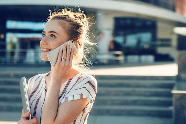 Encantadora mujer joven con pelo rojo y pecas hablando por teléfono al aire libre contra un edificio de negocios sosteniendo una computadora portátil contra la puesta de sol.