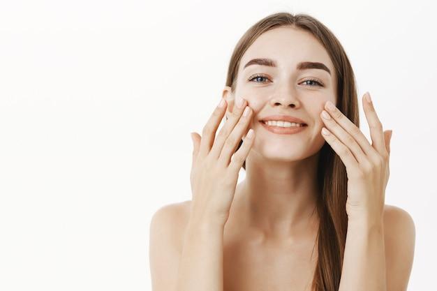 Encantadora mujer joven relajada y suave haciendo un procedimiento cosmetológico aplicando crema facial en la cara con los dedos y sonriendo ampliamente sintiéndose perfecta, cuidando la piel