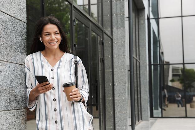 Encantadora mujer joven en ropa casual bebiendo café para llevar y sosteniendo el teléfono celular mientras está de pie sobre el edificio