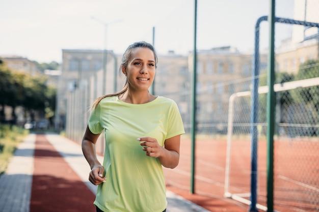 Encantadora mujer joven en ropa deportiva para correr en cinta en el estadio.