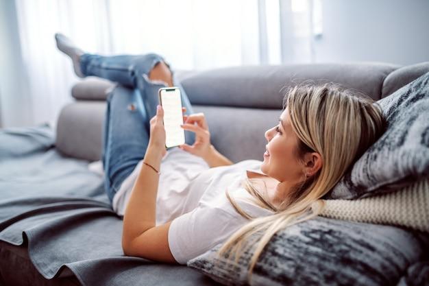 Encantadora mujer joven rubia caucásica vestida casual acostado en el sofá en la sala de estar, relajarse y usar el teléfono inteligente.