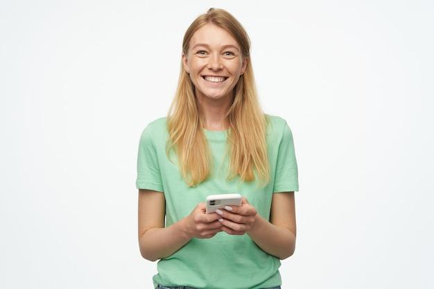 Encantadora mujer joven rubia, viste una camiseta verde, se siente feliz y sonríe ampliamente, mirando a la cámara y sosteniendo su teléfono
