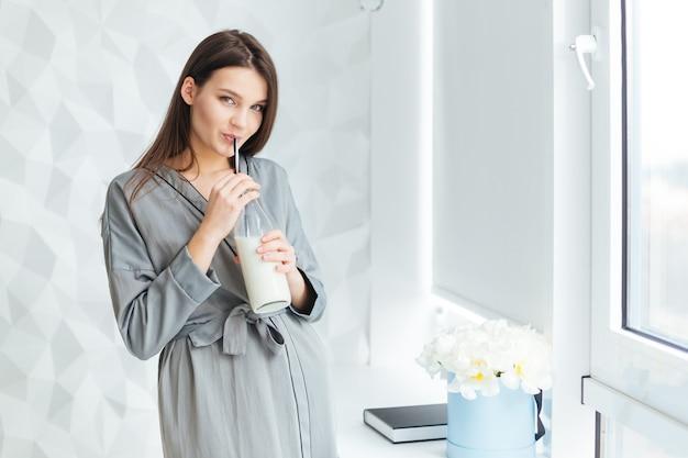 Encantadora mujer joven sensual en albornoz gris de pie y bebiendo leche fom botella con paja