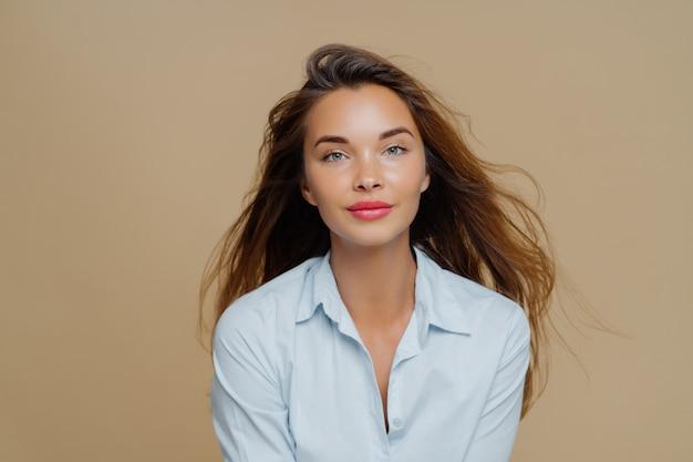 Encantadora mujer joven tiene el pelo largo y ondulado flotando en el viento, vestida con una elegante camisa azul