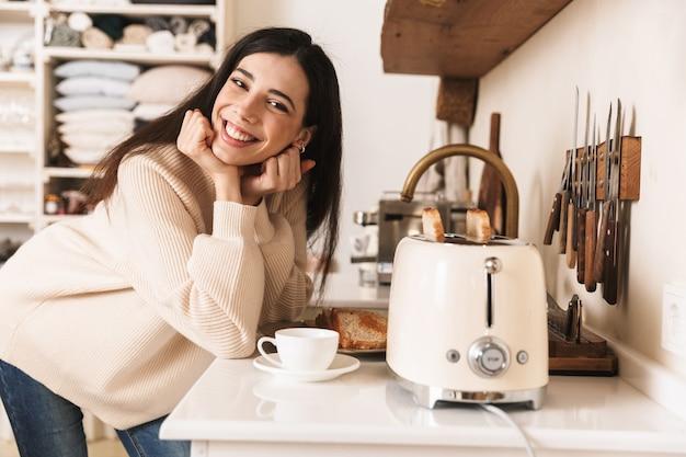 Encantadora mujer joven tomando una taza de café en la cocina, haciendo tostadas