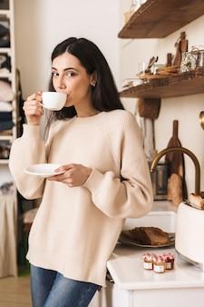 Encantadora mujer joven tomando una taza de café en la cocina