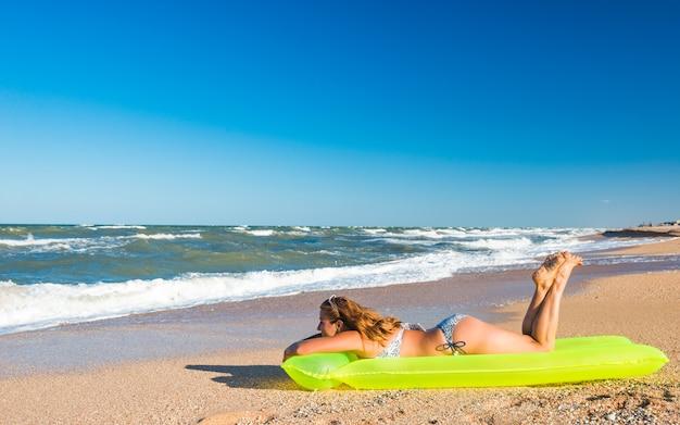 Encantadora mujer joven en traje de baño se encuentra en un colchón de aire y toma el sol después de nadar en el mar