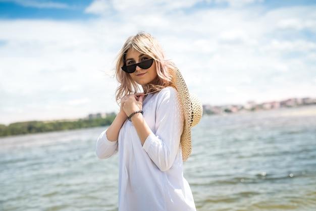 Encantadora mujer joven con un vestido blanco disfrutar de la naturaleza junto al lago en un día soleado. sesión de fotos de moda con estilo