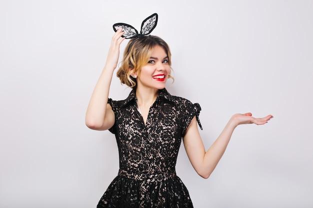 Encantadora mujer joven con vestido negro y corona negra, celebrando las fiestas, divirtiéndose, sonriendo y muestra la derecha.