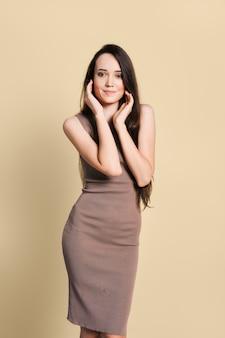 Encantadora mujer joven en vestido de punto ajustado, pelo largo y recto negro y zapatos de tacón posando en el estudio