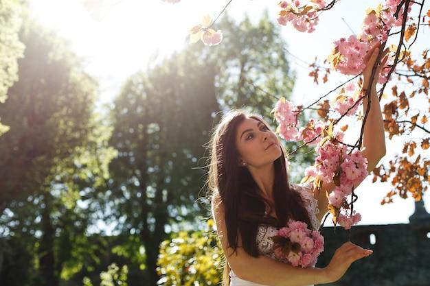 Encantadora mujer joven en vestido rosa posa ante un árbol de sakura lleno de flores rosadas