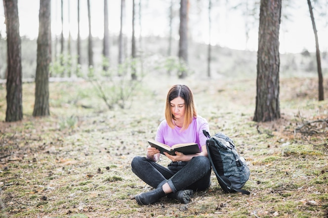 Encantadora mujer leyendo el libro en el bosque