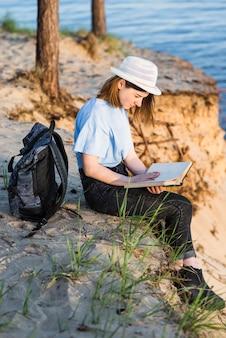 Encantadora mujer leyendo en el acantilado