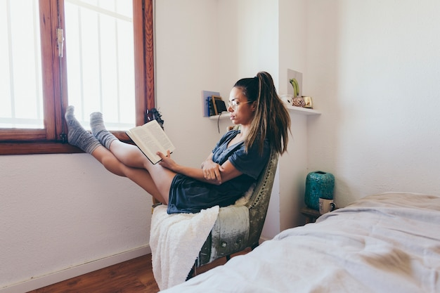 Encantadora mujer leyendo junto a la ventana