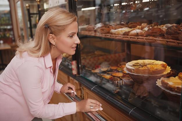 Encantadora mujer madura eligiendo pastel para comprar en la panadería local.