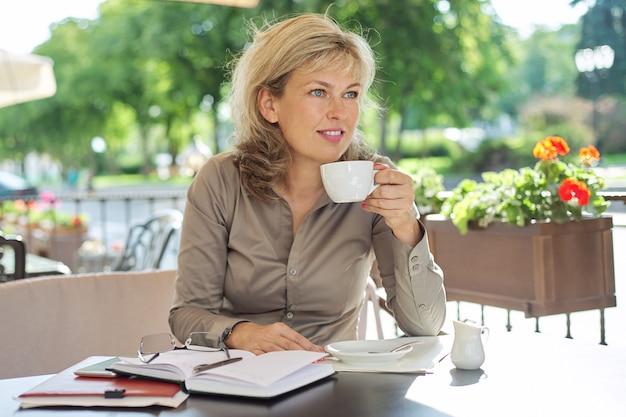 Encantadora mujer de mediana edad rubia con una taza de café en la cafetería al aire libre, mujer de negocios madura en la pausa para el café