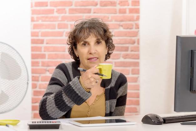 Encantadora mujer de mediana edad tomando un café