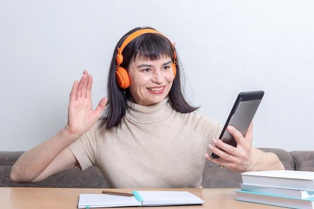 Encantadora mujer morena en auriculares naranjas con una videollamada y un gesto de saludo mientras está sentado en la mesa en casa