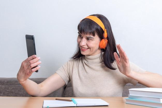 Encantadora mujer morena en auriculares naranjas con una videollamada y un gesto de saludo o adiós