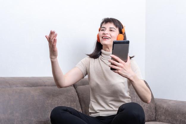 Encantadora mujer morena sentada en el sofá con auriculares naranjas con videollamada y gesticulando.