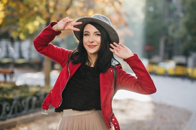 Encantadora mujer de pelo negro con expresión de cara feliz posando con el signo de la paz en la calle
