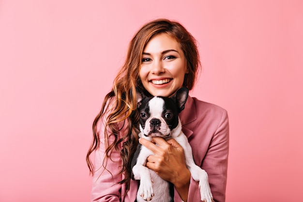 Encantadora mujer con pelo rojo brillante posando con su mascota. chica de buen humor en chaqueta rosa con perrito.