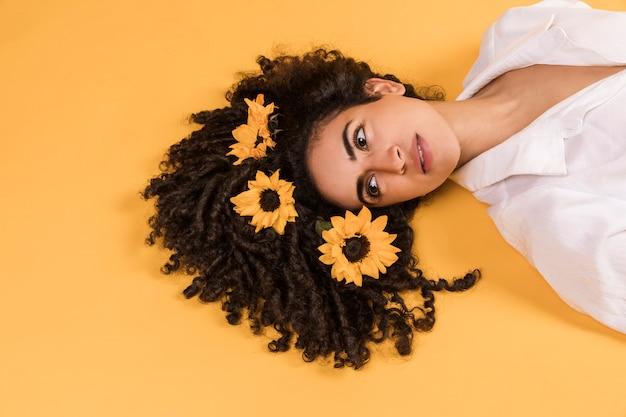 Encantadora mujer pensativa con flores en el pelo
