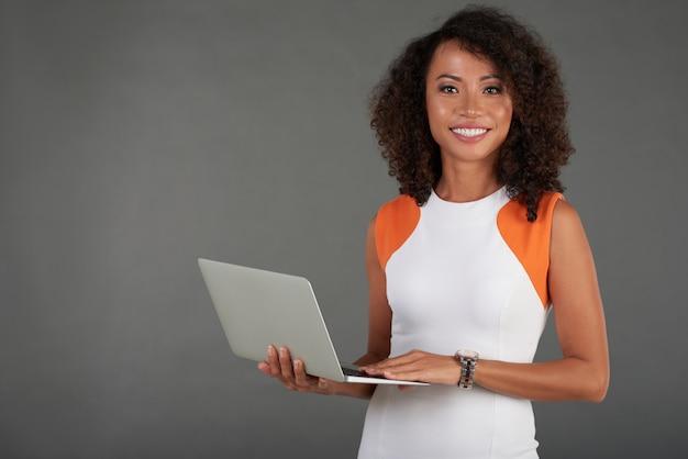 Encantadora mujer de pie con laptop y sonriendo