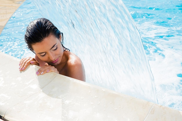 Encantadora mujer de pie en la piscina y relajarse bajo la cascada
