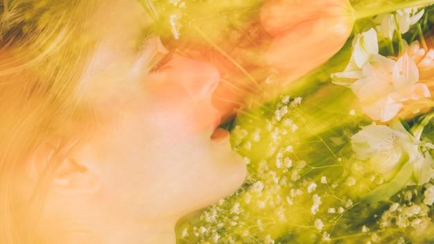 Encantadora mujer con ramo de flores en verdor.