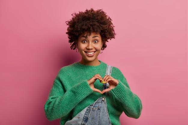 Encantadora mujer de raza mixta alegre confiesa enamorado, forma gesto de corazón con las manos
