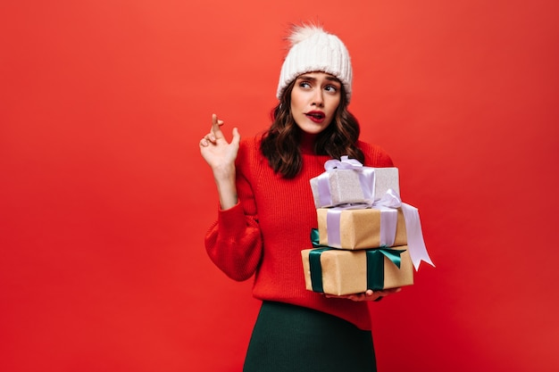 Encantadora mujer rizada sostiene cajas de regalo y cruza los dedos