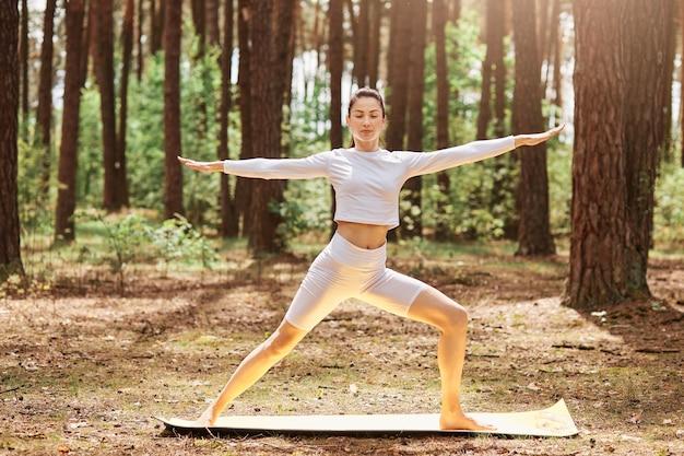 Encantadora mujer en ropa deportiva blanca practicando yoga en un parque verde o bosque, de pie en posición de yoga, manteniendo los ojos cerrados, extendiendo las manos a un lado, entrenando al aire libre.