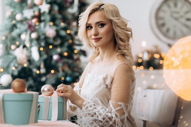 Encantadora mujer rubia abre cajas presentes sentadas ante un árbol de navidad