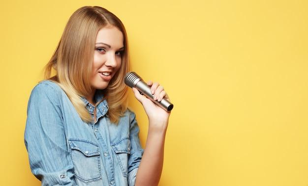 Encantadora mujer rubia cantando con micrófono en estudio sobre yel