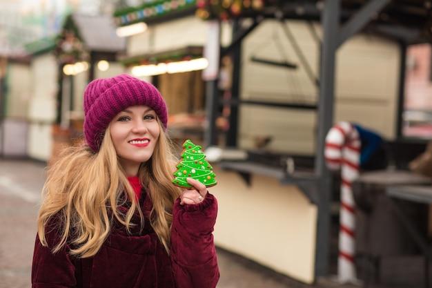 Encantadora mujer rubia comiendo deliciosas galletas de jengibre navideñas en la calle en kiev