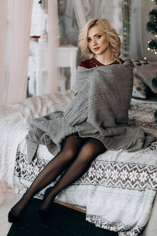 Encantadora mujer rubia se envuelve en una tela escocesa gris sentada en una cama antes de un árbol de navidad