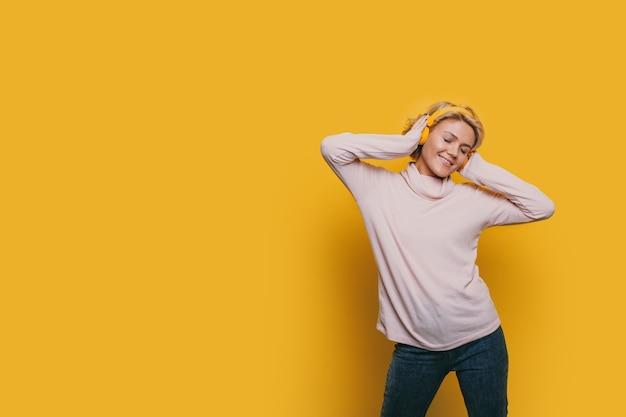 Encantadora mujer rubia escuchando música con auriculares en una pared de estudio amarillo con espacio libre