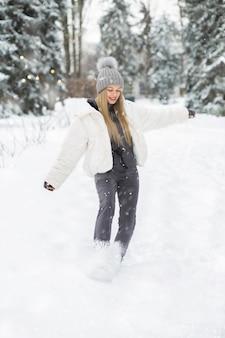 Encantadora mujer rubia jugando en el bosque durante las nevadas